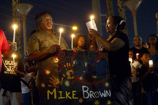 People hold candles during a vigil for Michael Brown at Martin Luther King Boulevard and Carey Avenue Thursday, Aug. 28, 2014. Brown, 18, was shot and killed by a police officer Aug. 9, 2014, in Ferguson, Mo.