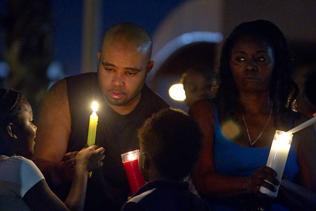 People light candles during a vigil for Michael Brown at Martin Luther King Boulevard and Carey Avenue Thursday, August 28, 2014. Brown, 18, was shot and killed by a police officer Aug. 9, 2014 in Ferguson, Mo.