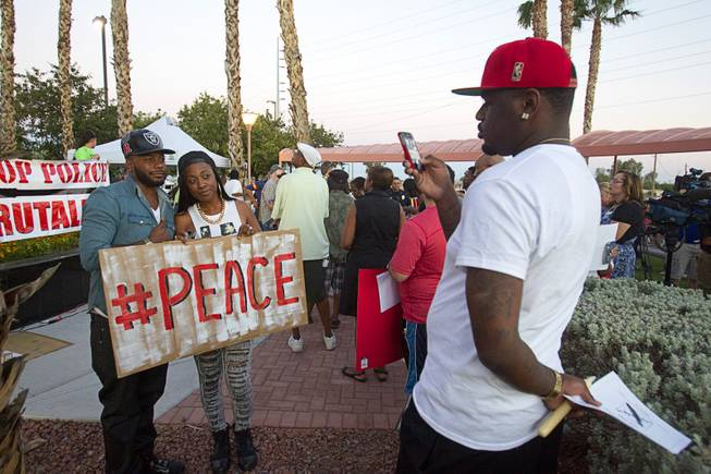 L.A.F. Fletcher and Moneka Majors pose for Phillip Shelton during a vigil for Michael Brown at Martin Luther King Boulevard and Carey Avenue Thursday, August 28, 2014. Brown, 18, was shot and killed by a police officer Aug. 9, 2014 in Ferguson, Mo.