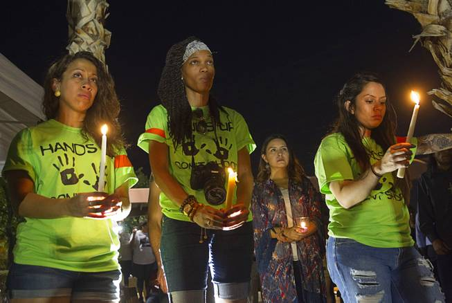 Organizers, from left, Briona Simons, Verise Johnson, and Liz Hernandez hold candles during a vigil for Michael Brown at Martin Luther King Boulevard and Carey Avenue Thursday, August 28, 2014. Brown, 18, was shot and killed by a police officer Aug. 9, 2014 in Ferguson, Mo.