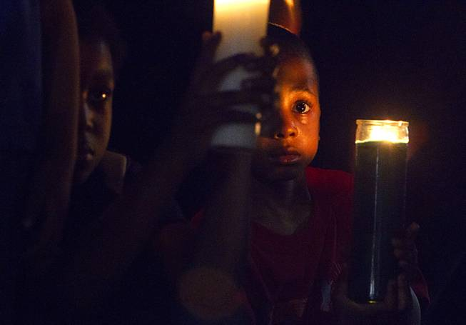 Lavel Burton, 5, holds a candle during a vigil for Michael Brown at Martin Luther King Boulevard and Carey Avenue Thursday, August 28, 2014. Brown, 18, was shot and killed by a police officer Aug. 9, 2014 in Ferguson, Mo.