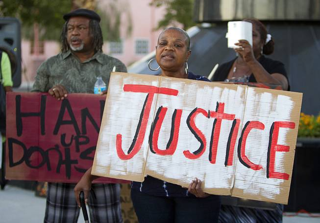 Sheila Taylor, center, holds a sign during a vigil for Michael Brown at Martin Luther King Boulevard and Carey Avenue Thursday, August 28, 2014. Brown, 18, was shot and killed by a police officer Aug. 9, 2014 in Ferguson, Mo.