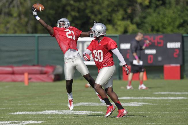 Ohio State wide receiver Parris Campbell, left, reaches for a ball as wide receiver Chris Fields defends during an NCAA college football practice Saturday, Aug. 9, 2014, in Columbus, Ohio.