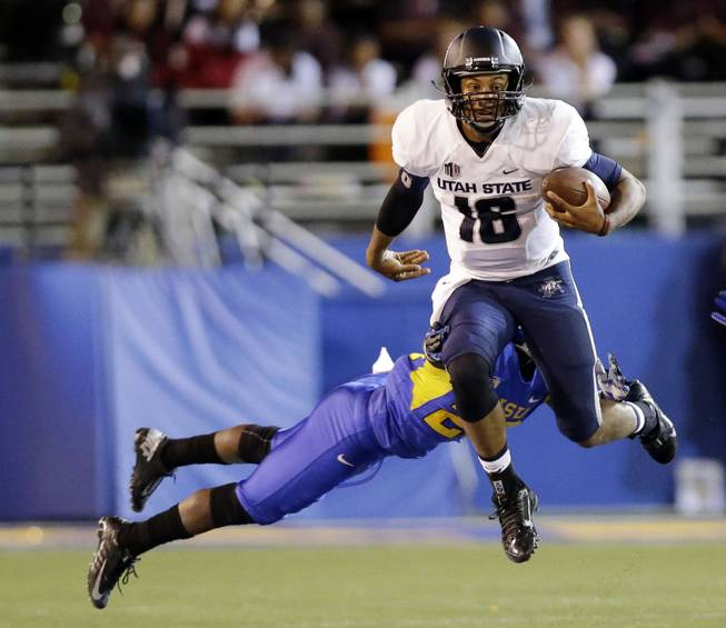 Utah State quarterback Chuckie Keeton (16) runs past San Jose State cornerback Chris Hill during the second half of an NCAA college football game on Friday, Sept. 27, 2013, in San Jose, Calif.