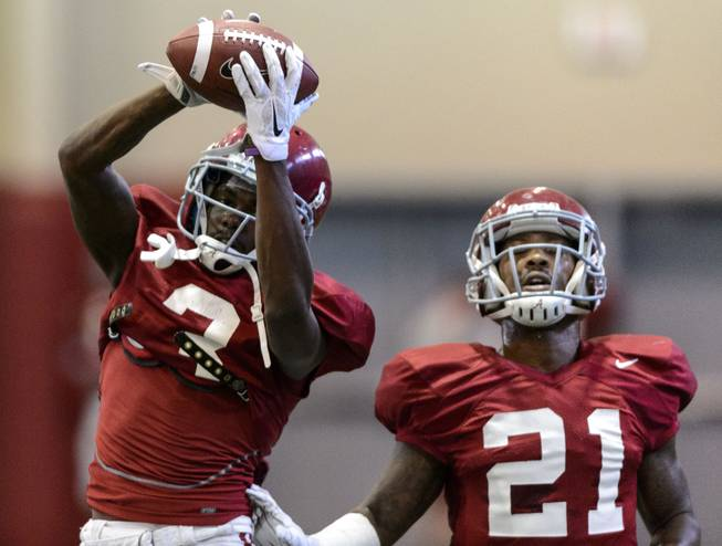 Alabama defensive back Bradley Sylve (3) grasps the ball during interception drills next to defensive back Maurice Smith (21) in Alabama's football practice, Tuesday, Aug. 26, 2014, in Tuscaloosa, Ala.