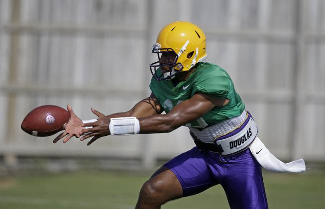 LSU quarterback Anthony Jennings (10) pitches out during their NCAA college football practice in Baton Rouge, La., Wednesday, Aug. 6, 2014.