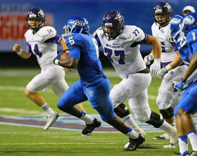 Georgia State linebacker Joseph Peterson runs back an interception of a pass by Abilene Christian quarterback Parker McKenzie, left rear, during the fourth quarter of an NCAA college football game in Atlanta on Wednesday, Aug. 27, 2014. The interception set up a Georgia State touchdown drive.