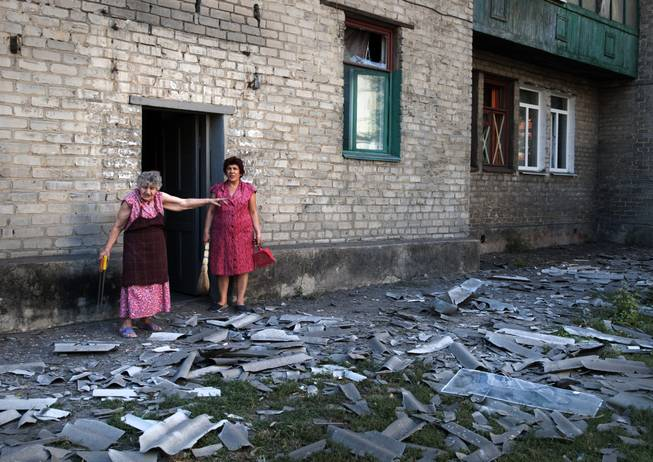 In this photo taken Wednesday, Aug. 27, 2014, local residents stand near the building where they live after a shelling in Donetsk, eastern Ukraine. Two columns of Russian tanks and military vehicles fired Grad missiles at a border post in southeastern Ukraine, then rolled into the country Thursday as Ukraine's overmatched border guards fled, a top Ukrainian official said.