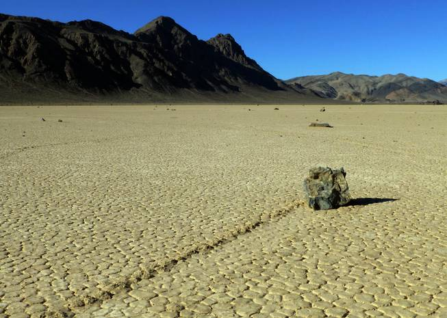 This undated photo provided by the National Park Service shows rocks that have moved across a dry lake bed in Death Valley National Park in California's Mojave Desert. For years scientists have theorized about how the large rocks — some weighing hundreds of pounds — zigzag across Racetrack Playa leaving long trails etched in the earth.