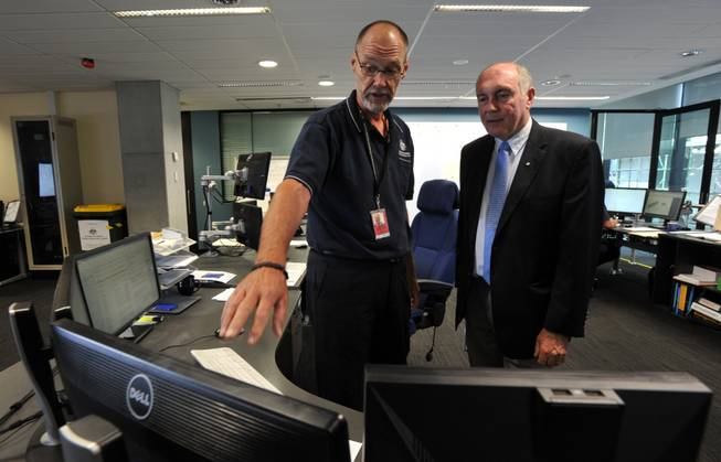 In this March 23, 2014, photo, Australian Deputy Prime Minister Warren Truss, right, talks with John Rice, senior search and rescue officer and mission coordinator for the search for the missing Malaysia Airlines Flight MH370, at rescue coordination center of the Australian Maritime Safety Authority in Canberra.