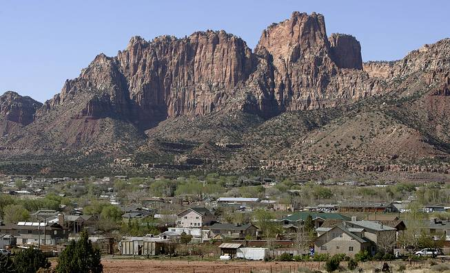 In this April 20, 2006, photo, Hildale, Utah, sits at the base of Red Rock Cliff mountains with its sister city, Colorado City, Ariz., in the foreground.