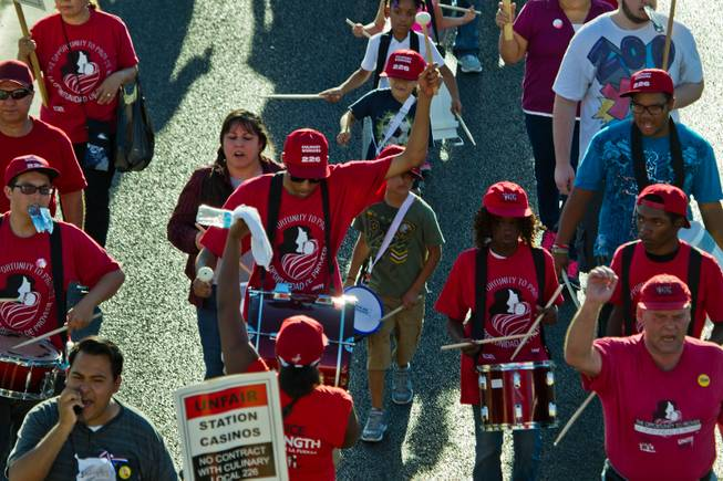 Adult and child drummers join in the march with culinary and bartender union members to Boulder Station to rally in support of fair jobs on Friday, August 29, 2014.