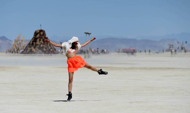 In this Aug. 27, 2014 photo, Franziska Goltz dances on the playa at Burning Man on the Black Rock Desert of Gerlach, Nev. Organizers call Burning Man the largest outdoor arts festival in North America, with its drum circles, decorated art cars, guerrilla theatrics and colorful theme camps.