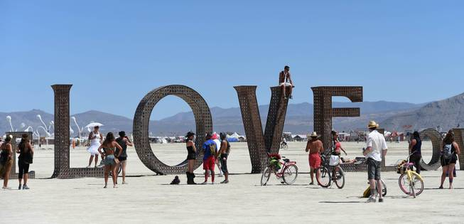 In this Aug. 27, 2014 photo, participants walk around at the Burning Man festival on the Black Rock Desert of Gerlach, Nev. Organizers call Burning Man the largest outdoor arts festival in North America, with its drum circles, decorated art cars, guerrilla theatrics and colorful theme camps.