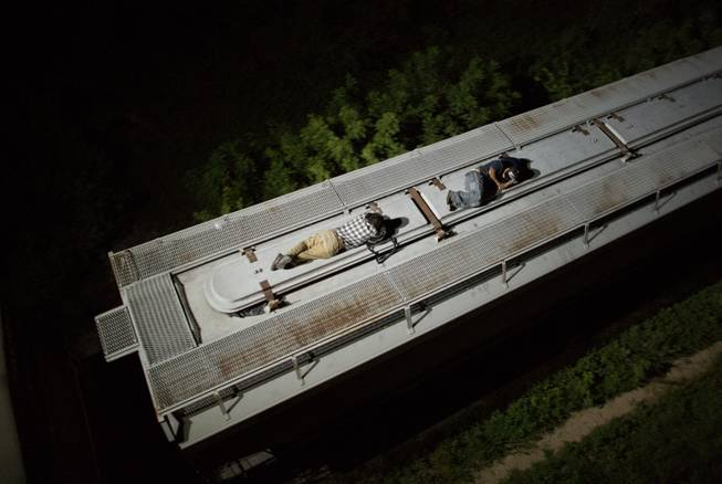 "In this Aug. 26, 2014 photo, Central American migrants sleep atop a moving freight train as it heads north from Arriaga toward Chahuites, Mexico. A Mexican crackdown seems to be keeping women and children off the deadly train, known as ""The Beast,"" that has traditionally helped thousands of migrants head north. The once-open route to the United States has become so difficult that trains now carry a small fraction of the migrants they used to, and almost exclusively adult men."