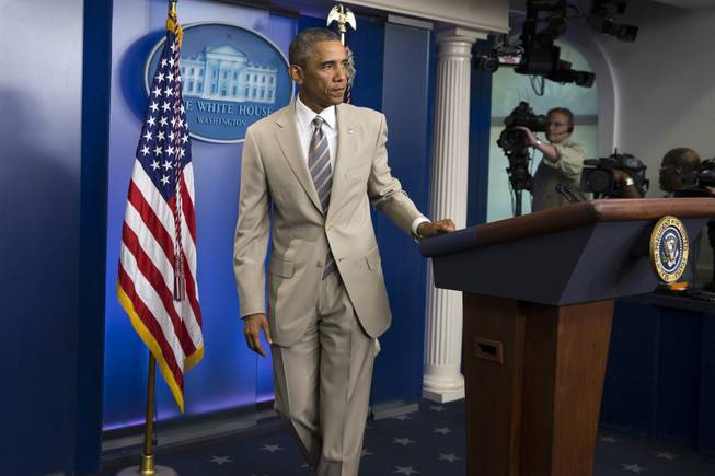 In this Thursday, Aug. 28, 2014, photo, President Barack Obama leaves after speaking about the economy, Iraq and Ukraine in the James Brady Press Briefing Room of The White House in Washington, D.C., before convening a meeting with his national security team on the militant threat in Syria and Iraq. Obama's summer fashion choice, not unprecedented among presidents — himself included — was the talk of social media Thursday. Other presidents who have taken on tan include Bill Clinton, Ronald Reagan, George H. W. Bush, George W. Bush and Dwight Eisenhower.