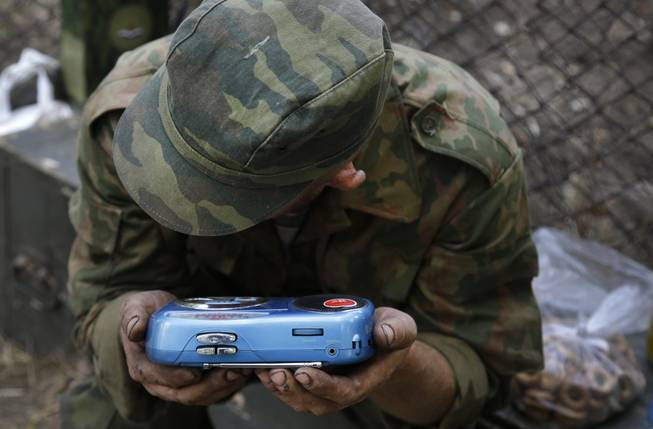 A pro-Russian rebel listens to the news on a transistor radio in the town of Novoazovsk, in eastern Ukraine, Friday, Aug. 29, 2014. In Novoazovsk, pro Russian rebel fighters looked to be in firm control, well-equipped and relaxed. At least half a dozen tanks were seen on roads around the town, although the total number at the rebels' disposal is believed to be much greater. Novoazovsk fell swiftly to the rebels Wednesday after being pounded by shelling.