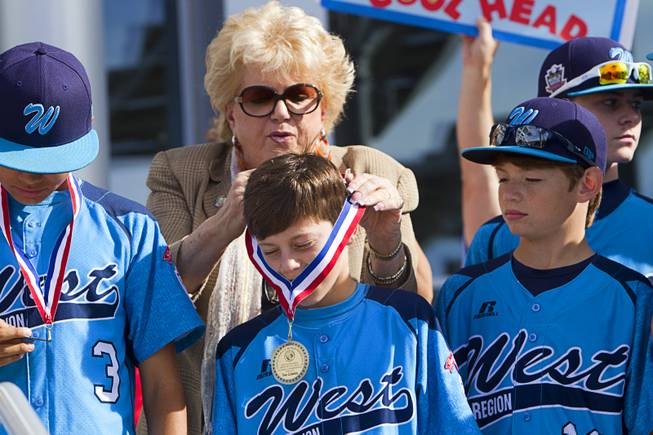Las Vegas Mayor Carolyn Goodman hangs medals on members of the Mountain Ridge Little League team at Las Vegas City Hall Saturday, Aug. 30, 2014. After the ceremony, the team boarded an open-air Big Bus for a police-escorted parade down the Las Vegas Strip.