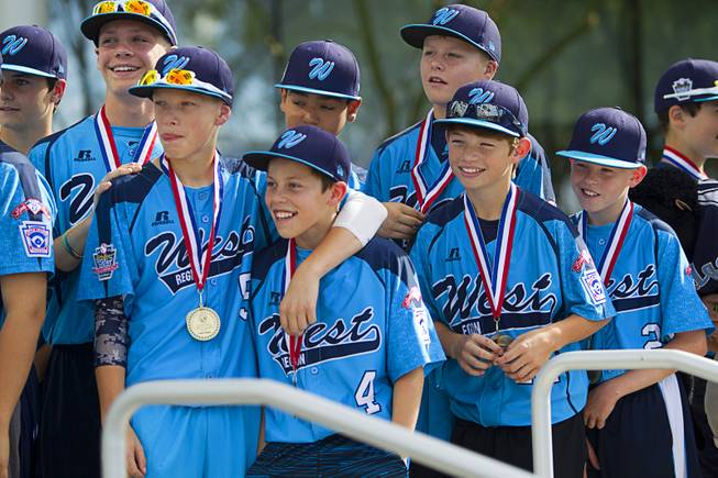 Members of the Mountain Ridge Little League team listen to coach Bob Kryszczuk during a ceremony at Las Vegas City Hall Saturday, Aug. 30, 2014. After the ceremony, the team boarded an open-air Big Bus for a police-escorted parade down the Las Vegas Strip.
