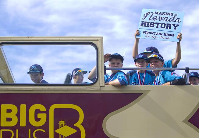 Members of the Mountain Ridge Little League team board a double-decker, open-air Big Bus following a ceremony at Las Vegas City Hall Saturday, Aug. 30, 2014.