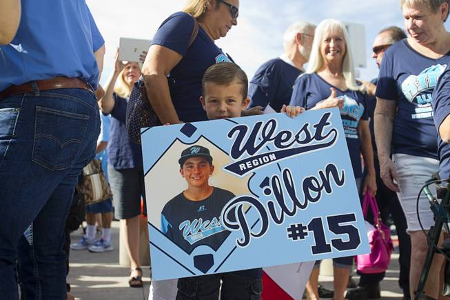 Leif Colvin holds a sign for third baseman Dillon Jones during a ceremony honoring the Mountain Ridge Little League team at Las Vegas City Hall Saturday, Aug. 30, 2014. After the ceremony, the team boarded an open-air Big Bus for a police-escorted parade down the Las Vegas Strip.