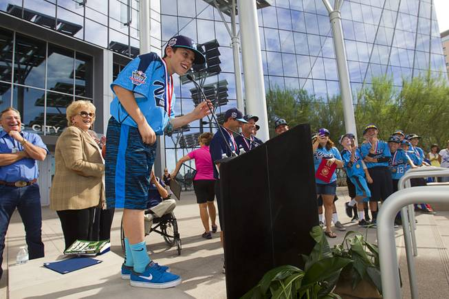 Second baseman Drew Laspaluto stands on a wall in order to reach the microphone during a ceremony honoring the Mountain Ridge Little League team at Las Vegas City Hall Saturday, Aug. 30, 2014. After the ceremony, the team boarded an open-air Big Bus for a police-escorted parade down the Las Vegas Strip.