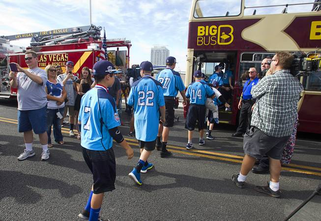 Players head to a double-decker, open-air Big Bus during a ceremony honoring the Mountain Ridge Little League team at Las Vegas City Hall Saturday, Aug. 30, 2014. After the ceremony, the team boarded an open-air Big Bus for a police-escorted parade down the Las vegas Strip.