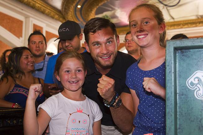Boxer Chris Algieri of Huntington, N.Y. poses with Australian tourists Hannah Hahn, left, 7, and her sister Ebony,10, at the Venetian Saturday, Aug. 30, 2014. Algieri and Manny Pacquiao of the Philippines are on day six of an international tour promoting their WBO welterweight title fight in Macau, China on November 22, 2014.