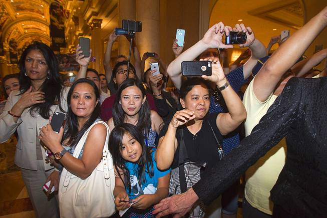 Fans of Filipino boxer Manny Pacquiao try to get his photo as he arrives at the Venetian Saturday, Aug. 30, 2014. Pacquiao and his opponent and Chris Algieri of Huntington, N.Y. are on day six of an international tour promoting their WBO welterweight title fight in Macau, China on November 22, 2014.