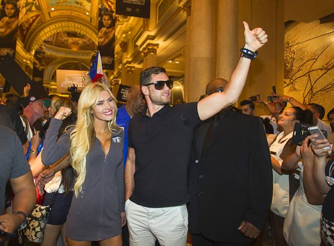 Boxer Chris Algieri of Huntington, N.Y. gives a thumbs-up as he arrives at the Venetian Saturday, Aug. 30, 2014. Accompanying Algieri is Jessica Hubbard, a Top Rank Boxing Knockout girl. Algieri and Manny Pacquiao of the Philippines are on day six of an international tour promoting their WBO welterweight title fight in Macau, China on November 22, 2014.