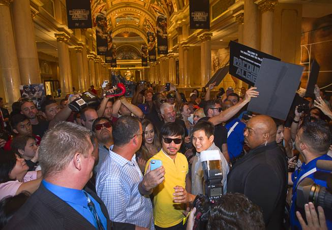 Boxer Manny Pacquiao, center, of the Philippines takes a selfie with a fan as he arrives at the Venetian Saturday, Aug. 30, 2014. Pacquiao and his opponent Chris Algieri of Huntington, N.Y. are on day six of an international tour promoting their WBO welterweight title fight in Macau, China on November 22, 2014.