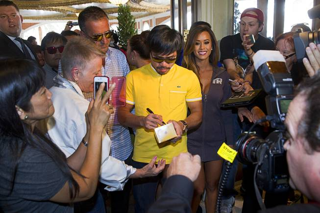 Boxer Manny Pacquiao of the Philippines signs autographs as he arrives at the Venetian Saturday, Aug. 30, 2014. Pacquiao and his opponent Chris Algieri of Huntington, N.Y. are on day six of an international tour promoting their WBO welterweight title fight in Macau, China on November 22, 2014.