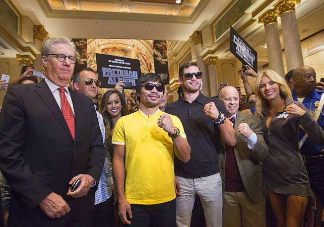Boxers Manny Pacquiao, left, of the Philippines and Chris Algieri of Huntington, N.Y. pose in the Venetian Saturday, Aug. 30, 2014. With the boxers are Edward Tracy, left, president/CEO of Sands China, and Scott Messinger, right, corporate vice president of advertising & brand management at Las Vegas Sands. The boxers are on day six of an international tour promoting their WBO welterweight title fight in Macau, China on November 22, 2014.