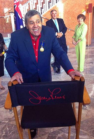 Jerry Lewis mugs behind his famous director's chair at the Smith Center for the Performing Arts on Friday, Aug. 29, 2014, as he is admitted as a Member of the Order of Australia, the highest civilian honor awarded by that country. Lewis was recognized for his work with the Muscular Dystrophy Foundation of Australia.
