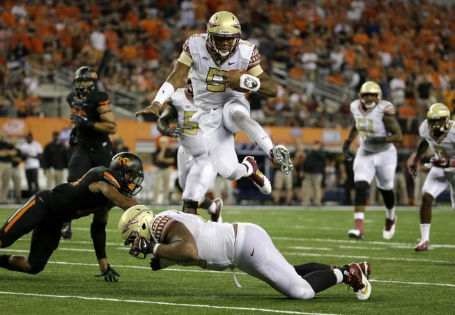 Florida State quarterback Jameis Winston leaps over guard Josue Matias as Oklahoma State safety Jordan Sterns, left, is unable to stop Winston from reaching the end zone for a touchdown in the second half of an NCAA football game Saturday, Aug. 30, 2014, in Arlington, Texas.