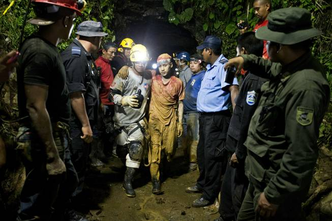 Miner Leber Vivas Gonzales, 16, center right, walks with his his arm over the shoulders of a rescue worker after he was rescued from the El Comal gold and silver mine in Bonanza, Nicaragua, late Friday, Aug. 29, 2014. Nicaraguan rescuers have saved 22 of at least 26 workers trapped in a mine collapse and were working Saturday to free the rest, officials said.