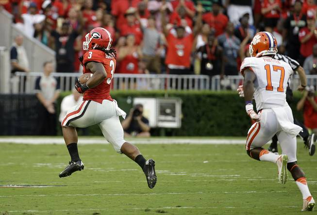 Georgia's Todd Gurley, left, breaks away from Clemson's Kyrin Priester to return a kickoff for a touchdown in the first half of an NCAA football game Saturday, Aug. 30, 2014, in Athens, Ga.