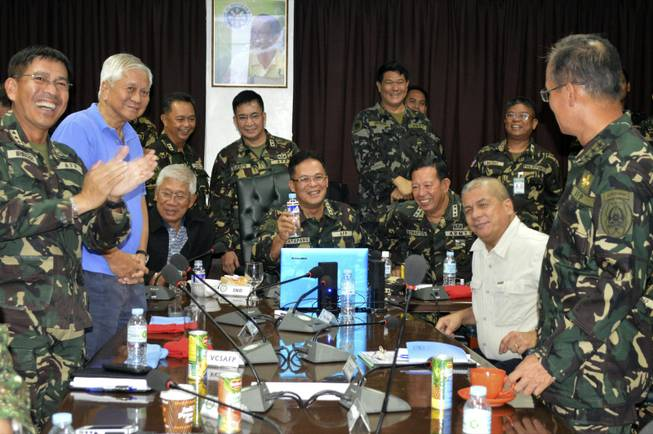In this photo released by the Armed Forces of the Philippines Public Affairs Office, Philippine Military Chief Gen. Gregorio Catapang, center, reacts after learning about the safe repositioning of Filipino peacekeepers in Golan Heights as they monitor the situation with Philippine Foreign Affairs Secretary Albert Del Rosario, second left, Philippine National Defense Secretary Voltaire Gazmin, third from left seated, at Camp Aguinaldo military headquarters in suburban Quezon city, Philippines, on Saturday, Aug. 30, 2014.