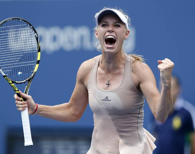 Caroline Wozniacki of Denmark reacts after defeating Maria Sharapova, of Russia, during the fourth round of the 2014 U.S. Open tennis tournament, Sunday, Aug. 31, 2014, in New York.