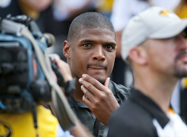 Former Missouri player Michael Sam watches pregame festivities before the start of the South Dakota State-Missouri NCAA college football game Saturday, Aug. 30, 2014, in Columbia, Mo. Sam, the first openly gay player drafted by an NFL team, was released by St. Louis Rams Saturday.