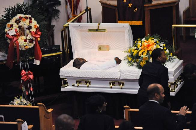 FILE - In this July 23, 2014 file photo, Eric Garner's body lies in a casket during his funeral at Bethel Baptist Church in the Brooklyn borough of New York. Garner died in police custody after an officer placed him in an apparent chokehold. Staten Island District Attorney Daniel Donovan announced Tuesday, Aug. 19, 2014, that an extra grand jury will be impaneled to hear evidence next month in the July 17 death of Garner. Donovan says his decision is based on his office's investigation and the medical examiner's ruling that the death was homicide.