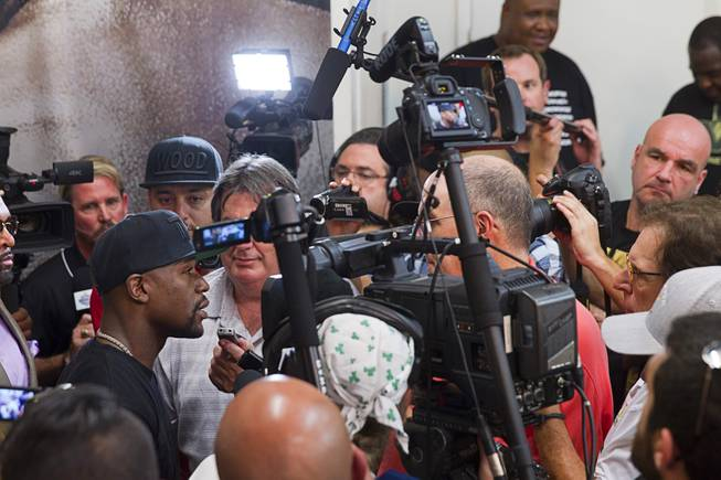 WBC/WBA welterweight champion Floyd Mayweather Jr. is surrounded by reporters and photographers during a media day at the Mayweather Boxing Club Tuesday, Sept. 2, 2014. Mayweather will face Marcos Maidana of Argentina in a rematch at the MGM Grand Garden Arena on Saturday, Sept. 13.