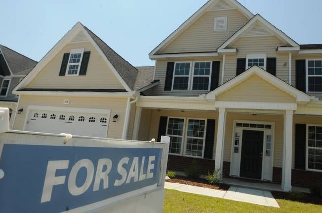 FILE - This June 19, 2014, file photo, shows a home for sale in Wilmington, N.C. Real estate data provider CoreLogic reports on U.S. home prices in July. In June, prices rose by the smallest year-over-year amount in 20 months, slowed by modest sales and more properties coming on the market. The slowing increases should make homes more affordable after prices had risen sharply last year. At the same time, Americans' pay hasn't risen nearly as fast.