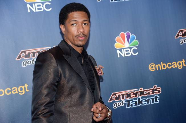"FILE - In a Tuesday, July 29, 2014 file photo, host Nick Cannon arrives at the ""America's Got Talent"" pre-show red carpet at Radio City Music Hall, in New York. Scholastic announced Tuesday, Sept. 2, 2014 that Cannon's ""Neon Aliens Ate My Homework and Other Poems"", a book of poems for children, will be published in March 2015."