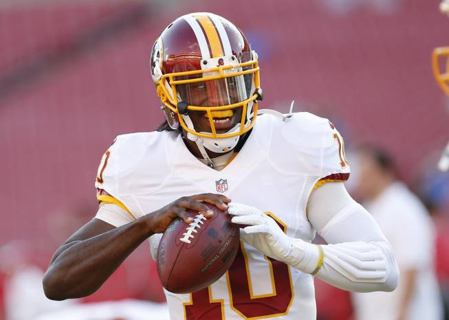 Washington Redskins quarterback Robert Griffin III (10) warms up before the start of a preseason NFL football game against the Tampa Bay Buccaneers Thursday, Aug. 28, 2014, in Tampa, Fla.