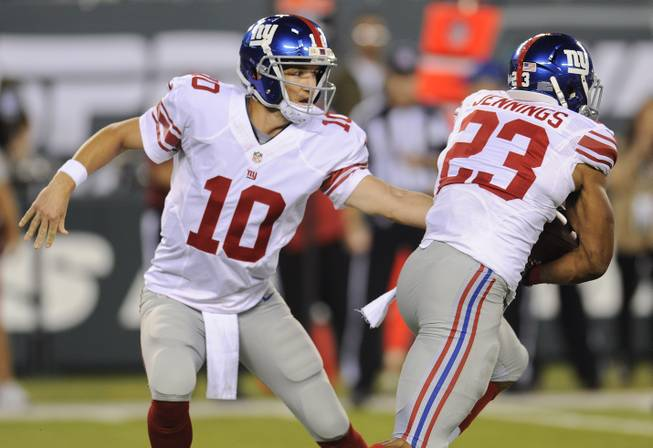 New York Giants quarterback Eli Manning (10) hands the ball off to running back Rashad Jennings (23) against the New York Jets in the first quarter of a preseason NFL football game, Friday, Aug. 22, 2014, in East Rutherford, N.J.