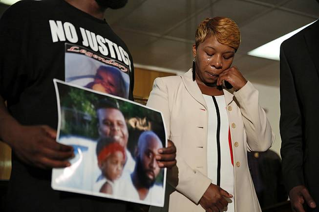 In this Aug. 11, 2014 file photo, Lesley McSpadden, the mother of 18-year-old Michael Brown, wipes away tears as Brown's father, Michael Brown Sr., holds up a family picture of himself, his son, top left, and a young child during a news conference in Jennings, Mo. Lingering questions about Michael Brown could be answered Wednesday as two news organizations seek the release of any possible juvenile records for the unarmed 18-year-old who was shot by a police officer last month.