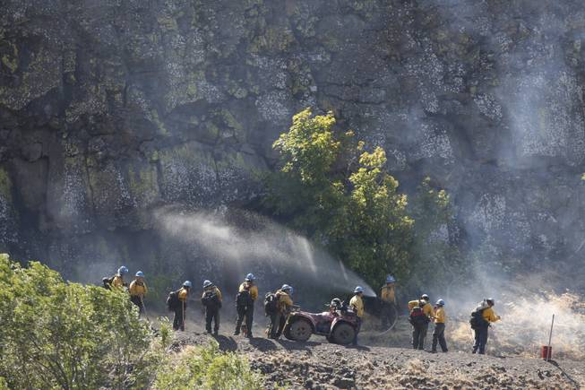 Firefighters stand along Highway 30 to assist back-burning efforts near The Dalles, Ore. on Friday morning, Aug. 8, 2014. Fire crews on both the ground and in the air set fires to burn off fuel sources in the path of the wind-driven Rowena fire, west of The Dalles.