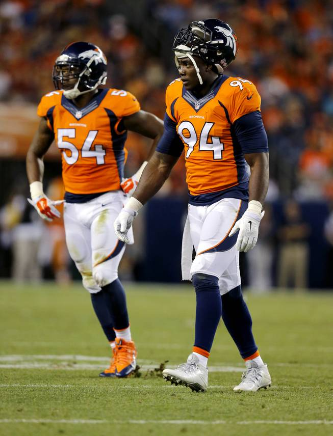 Denver Broncos defensive end DeMarcus Ware (94) and Brandon Marshall (54) walk to the bench during the first half of an NFL preseason football game against the Houston Texans, Saturday, Aug. 23, 2014, in Denver.