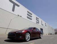 This June 22, 2012, photo shows a Tesla Model S electric sedan outside the Tesla factory in Fremont, Calif.